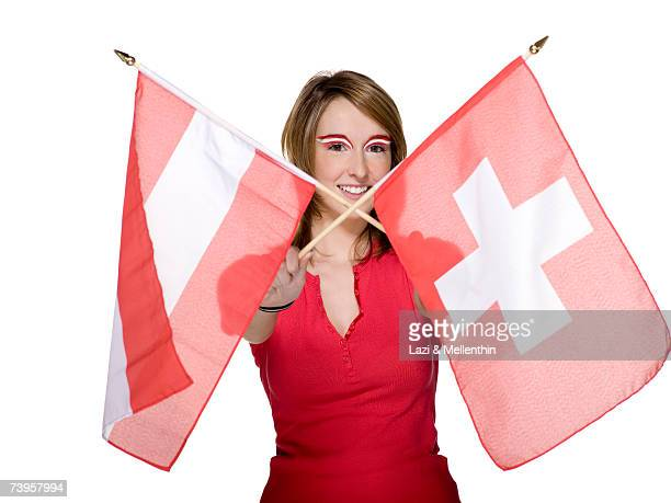 Woman crossing Austrian and Swiss flag, portrait, smiling