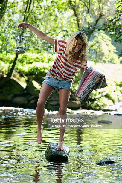 Woman crossing creek with camping gear