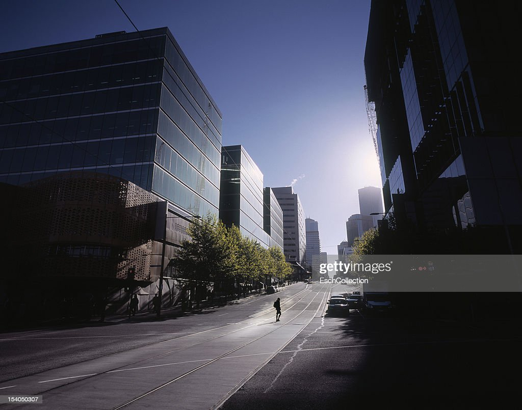 Woman crossing empty street in Melbourne at dawn