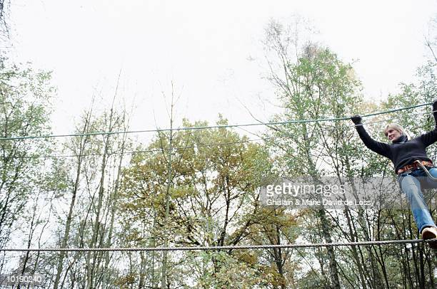 Woman crossing monkey bridge, low angle view