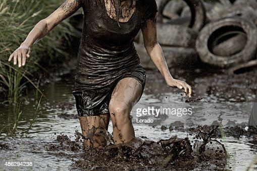 woman crossing mud obstacle