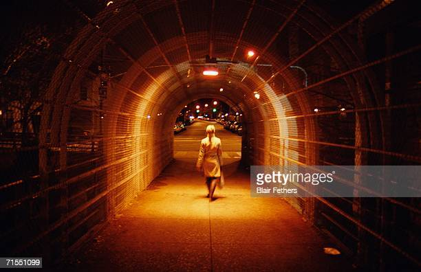 Woman crossing overpass at night