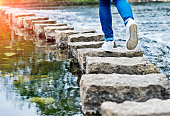 Woman crossing stepping stones on a river