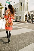 A woman crossing the street with shopping bags, Rodeo Drive, Los Angeles, California