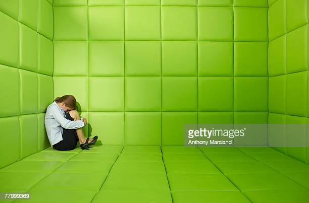 Woman crouched in a corner in a green padded cell