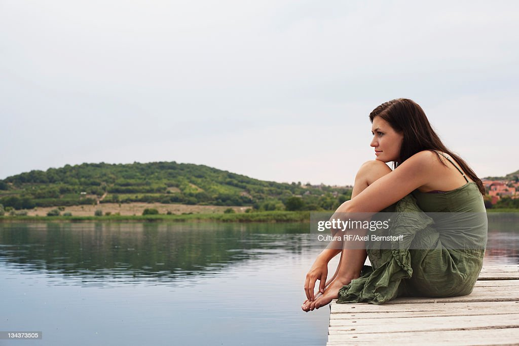 Woman crouched on pier : Stock Photo