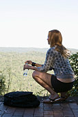 Woman crouching and observing scenery