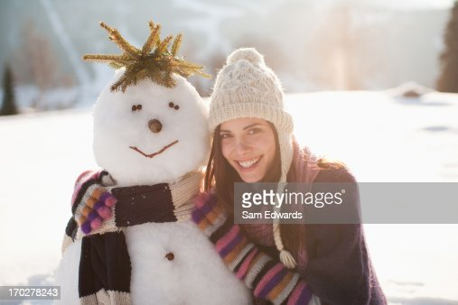 Woman crouching near snowman