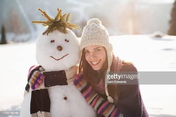 Woman crouching near snowman