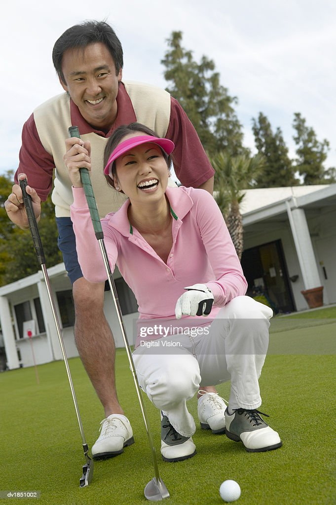 Woman Crouching on a Golf Course and a Man Standing Behind : Stock Photo