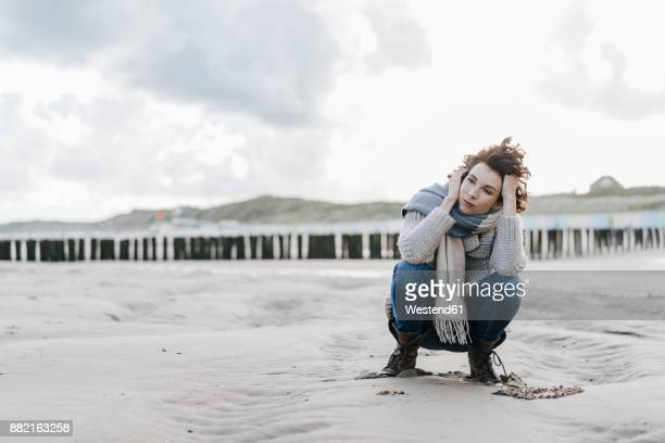 Woman crouching on the beach
