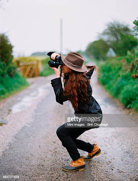 A woman crouching to take a photograph on a country road.
