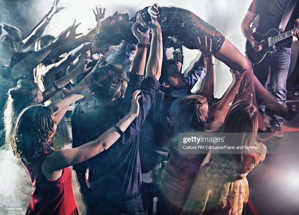 Woman crowdsurfing in club : Stock Photo
