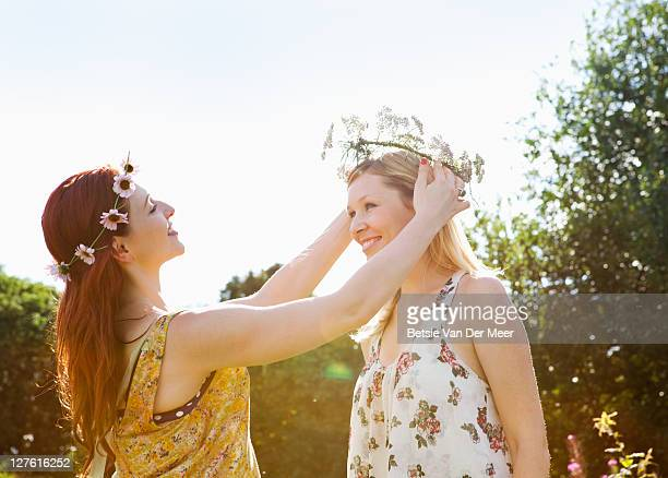 Woman crowning friend with a daisy chain.