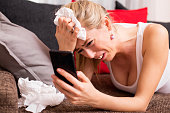 Woman crying while lying on couch with cellphone in her hand