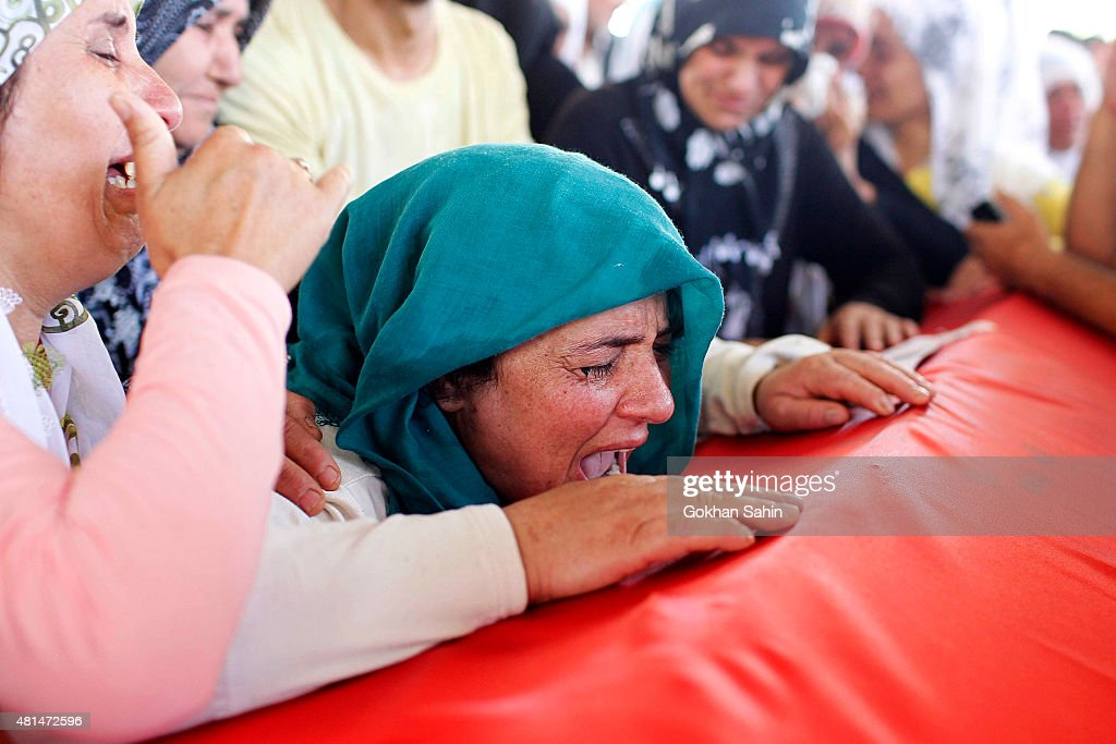 A woman crys over a coffin during a funeral ceremony for the victims of a suicide bomb attack yesterday which killed 32 people in the southern...