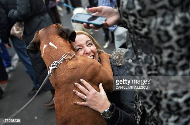 A woman cuddles a dog during a meeting against killings of stray dogs in Bucharest on March 8 2014 Authority for the Supervision and Protection of...