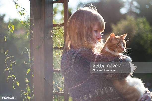 Woman cuddles cat in sunshine