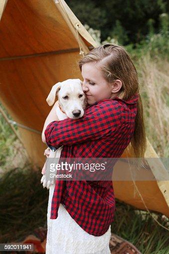 Woman cuddling dog near camping tent