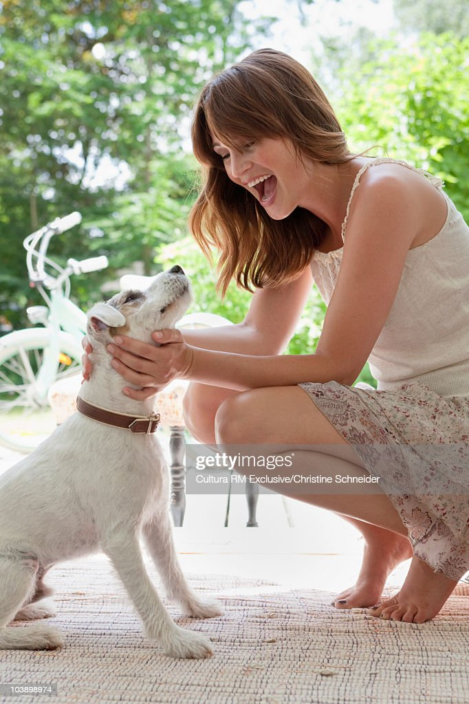 Woman cuddling her dog : Stock Photo