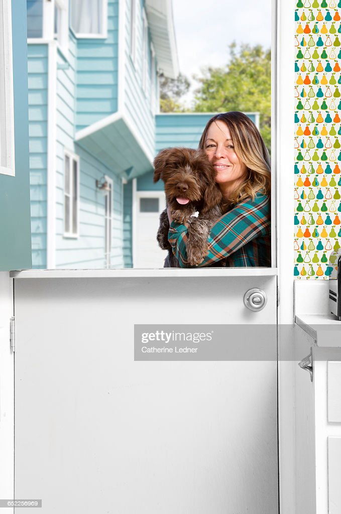 Woman cuddling with dog in half doorway