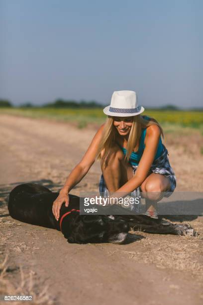 Woman cuddling with her dog on the road