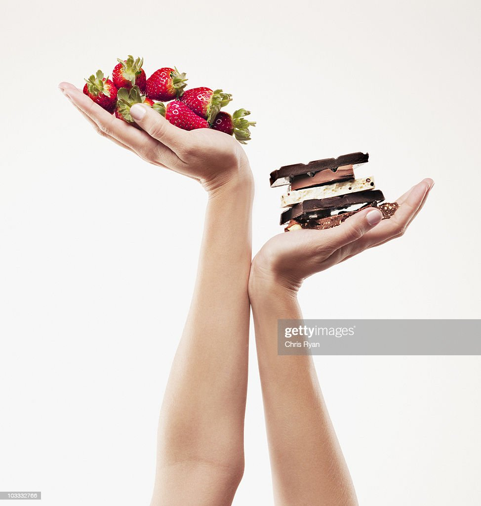 Woman cupping strawberries above chocolate bars : Stock Photo