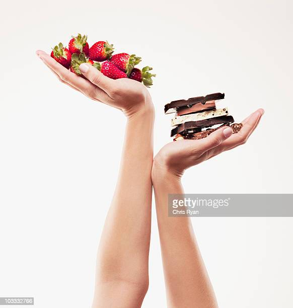 Woman cupping strawberries above chocolate bars