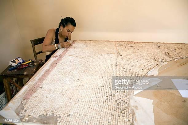 Woman curator repairing mosaic Archaeological museum Rhodes Greece