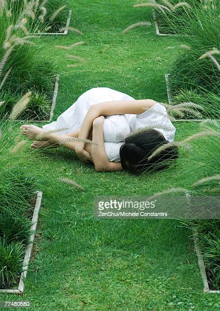 Woman curled up in fetal position on grass