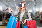 Woman customer experience virtual shopping thru modern headset and pointing finger at something