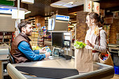 Young woman customer buying food, standing on the cash register with cheerful cashier in the supermarket