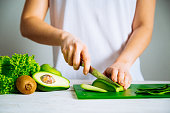 woman cut avocado. healthy food concept. ingredients for smoothies