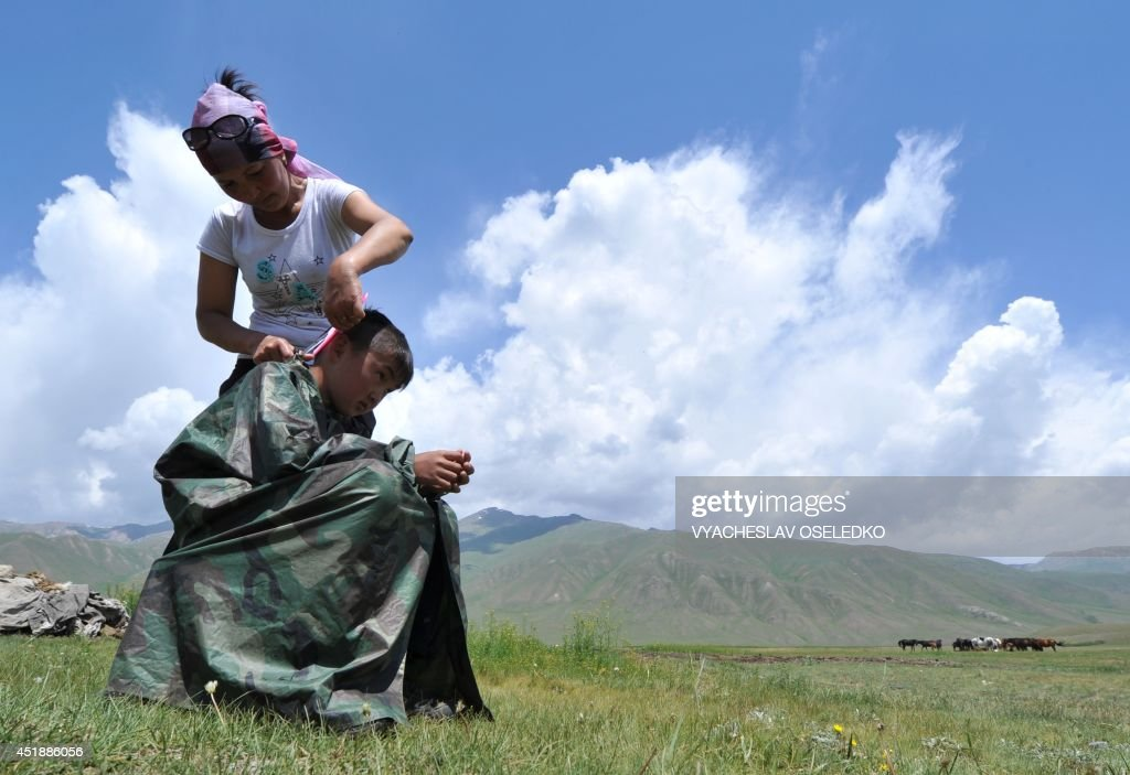 A woman cuts her son's hair outdoor at the Suu-Samyr plateau, 2,500 meters above the sea level, near the ancient Silk Road network of trade routes between the East and West, some 200 km outside Bishkek, the capital of Kyrgyzstan, on July 8, 2014. AFP PHOTO / VYACHESLAV OSELEDKO
