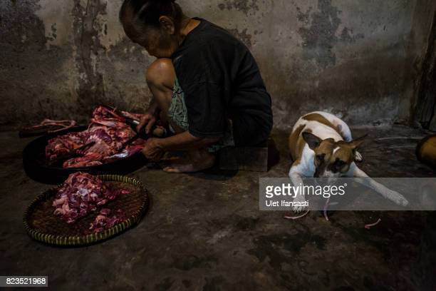 A woman cuts up dog meat as a dog eats some bones during the slaughter process at a dog meat butchery house on July 27 2017 in Yogyakarta Indonesia...