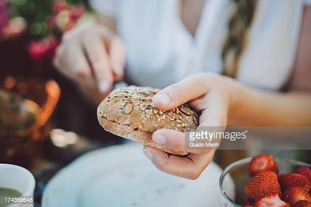 Woman cutting a bun open for breakfast.