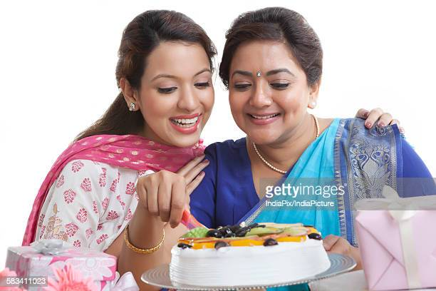 Woman cutting birthday cake while daughter looks on