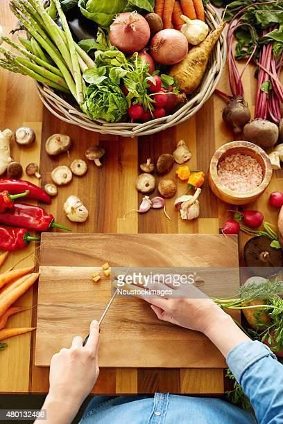 Woman cutting carrots on wooden board
