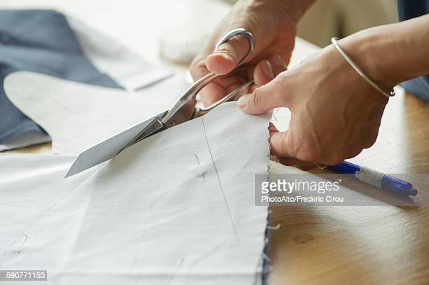 Woman cutting fabric, cropped