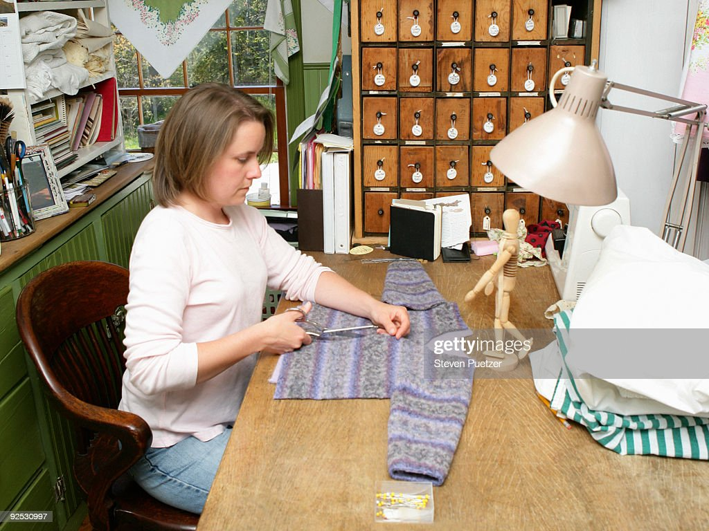 Woman cutting fabric for clothing : Stock Photo