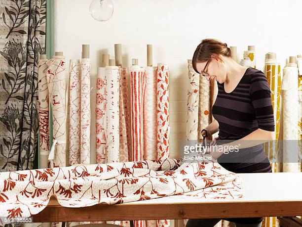 Woman cutting fabric on work table in hand-printed textile workshop