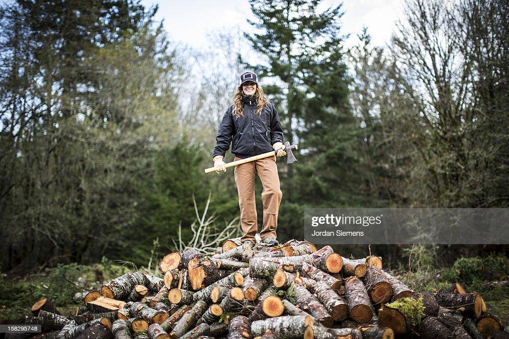 A woman cutting fire wood. : Stock Photo
