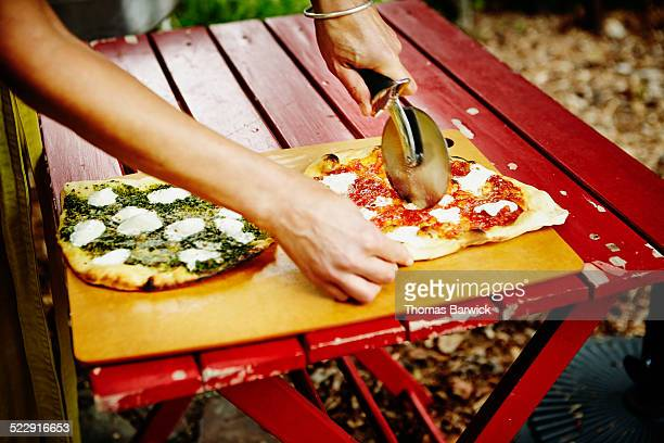 Woman cutting fresh wood fired pizzas