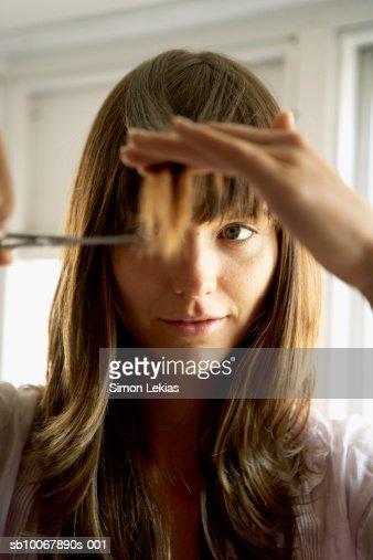 Donna taglio di capelli con forbici, primo piano