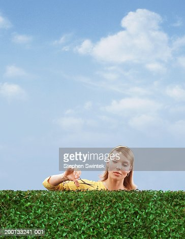 Woman cutting hedge with scissors