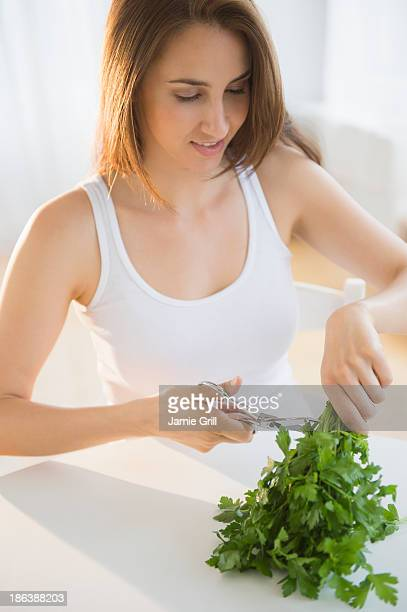 Woman cutting herbs with scissors