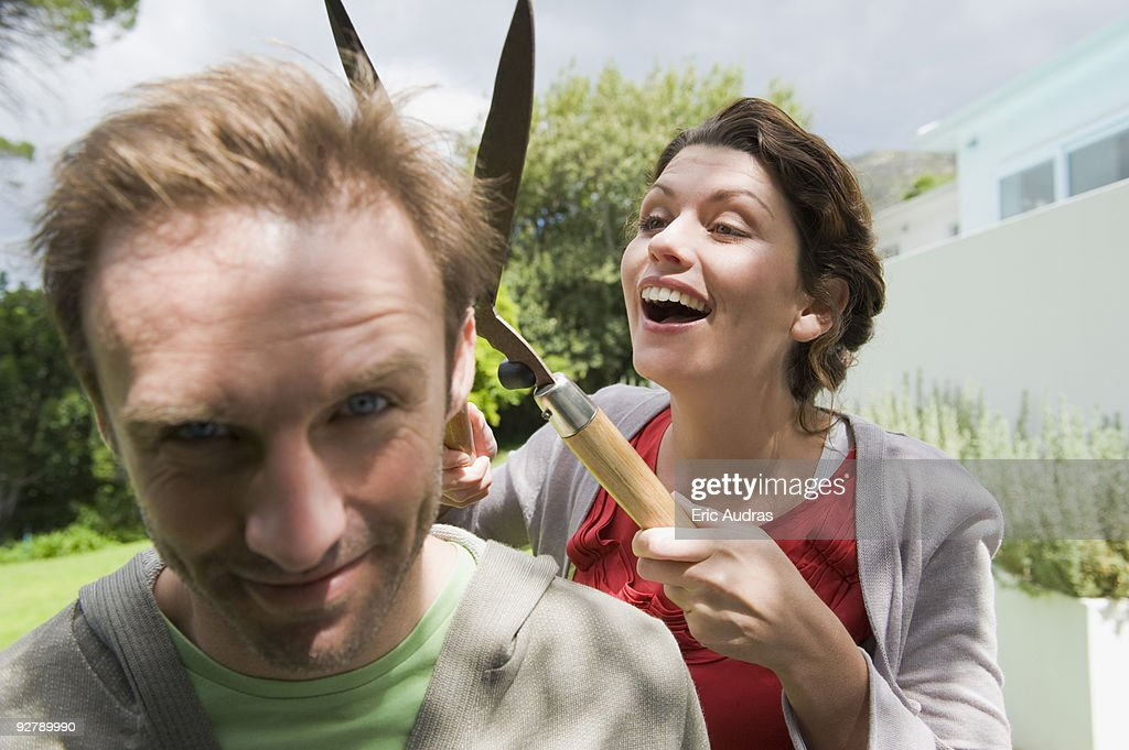 Woman cutting man's hair with a hedge clipper : Stock Photo