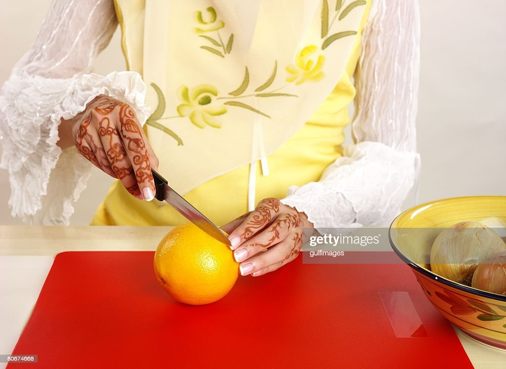 Woman cutting orange, midsection : Stock Photo