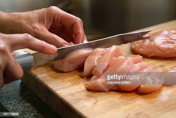 Woman Cutting Raw Chicken on a Wooden Cutting Board