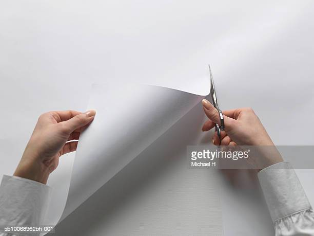 Woman cutting through white paper, close-up of hand